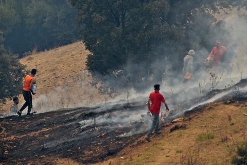 Voluntários tentam conter incêndio florestal nas colinas de Kabylie, a leste de Argel, capital da Argélia, 12 de agosto de 2021 [Ryad Kramdi/AFP via Getty Images]