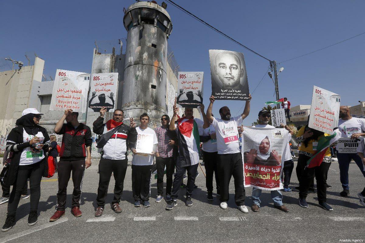 Um grupo de pessoas faz uma manifestação em frente ao muro de separação de Israel na Cisjordânia para mostrar seu apoio aos prisioneiros palestinos mantidos em celas israelenses, em 22 de março de 2019 [Wisam Hashlamoun/Agência Anadolu]