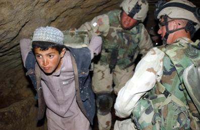 """Garoto afegão """"ajuda"""" a remover armas e munições encontradas dentro de uma casa durante a Operação Crackdown, na cidade de Khar Bolaq, no Afeganistão, por soldados do Exército dos EUA (EUA) parte da operação Liberdade Duradoura [Picryl/Public Domain]"""