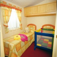 Crantock Holiday Home twin bedroom with travel cot at Monkey Tree Holiday Park near Newquay