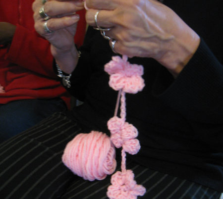 Attendee crochets a chain of blossoms