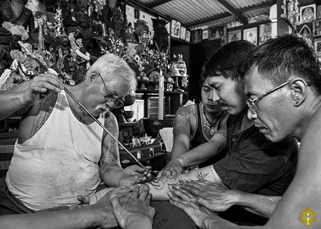 Great master ajarn Thong tattooing one of his student. Several helpers stretch the skin