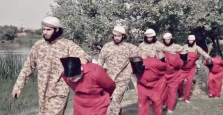 Blindfolded prisoner being led by ISIS fighters