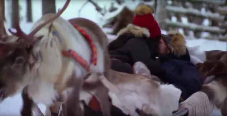 Nick cuddles up to one of the girls in a sled pulled by a reindeer in Inari-Saariselkä