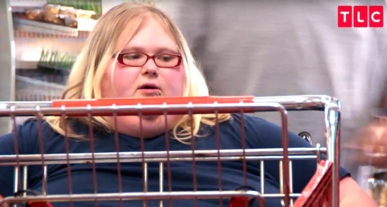 Nicole behind a trolley as she gets pushed around the store in her chair