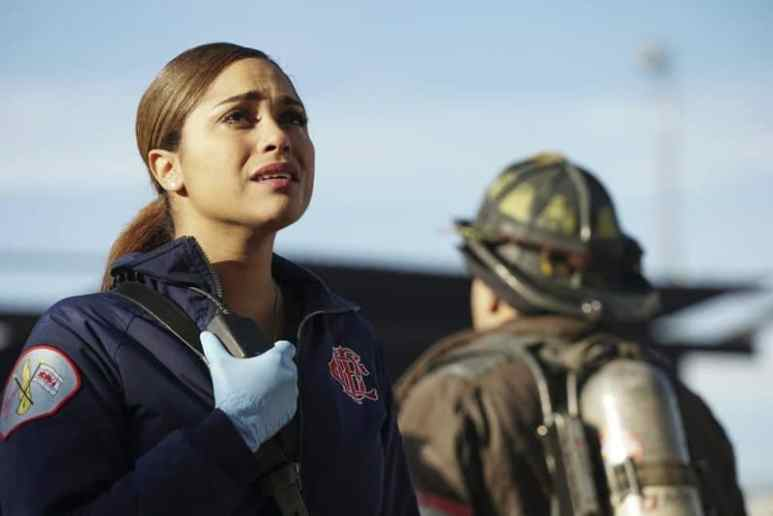 Monica Raymund as Dawson looking up at the building and holding her radio