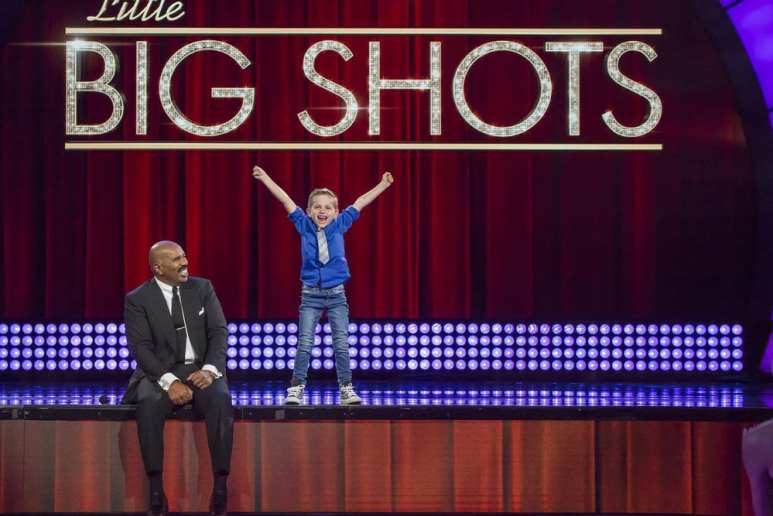 Nathan Bockstahler with his hands in the air as Steve Harvey sits on the edge of the Little Big Shots stage