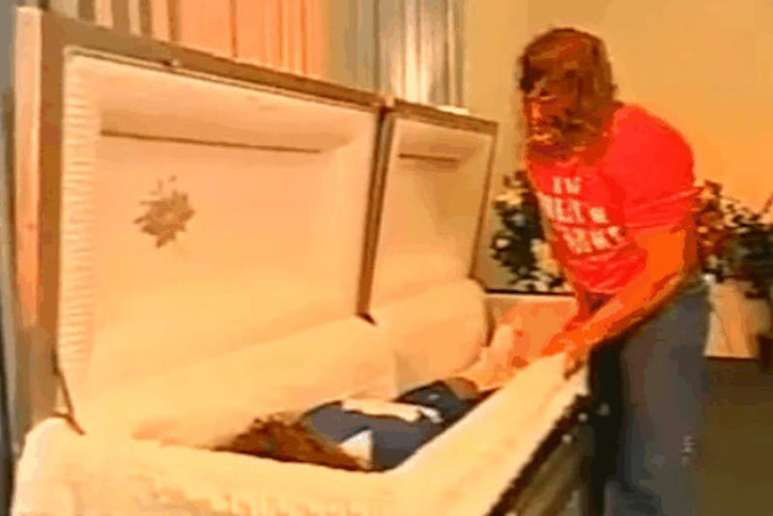 Kane sanding next to a coffin containing a dummy of Katie Vick