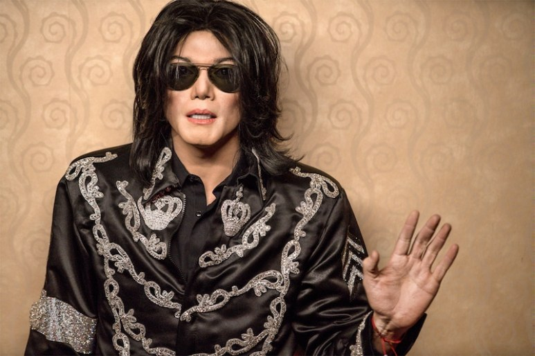 Navi, as Michale Jackson, raises his hand to the camera in Searching for Neverland