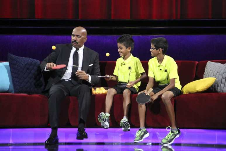 Table tennis prodigies Sid and Nandan Naresh sitting on the couch with host Steve Harvey on Little Big Shots