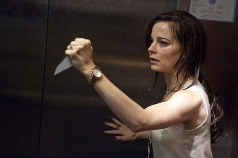 Bojana Novakovic holds up a sharp object inside an elevator in Devil