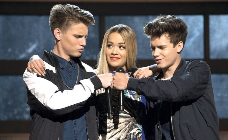 Contestants Jay Gilbert and Michael Conor punch fists as Rita Ora stands in between them on Boy Band