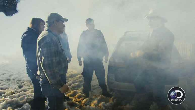 Marty Raney and the Hanson family standing by the car in smoke