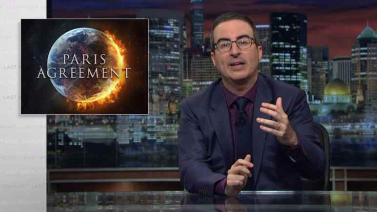 John Oliver on Last Week Tonight, with a picture of a flaming Earth and the words 'Paris Agreement' behind him