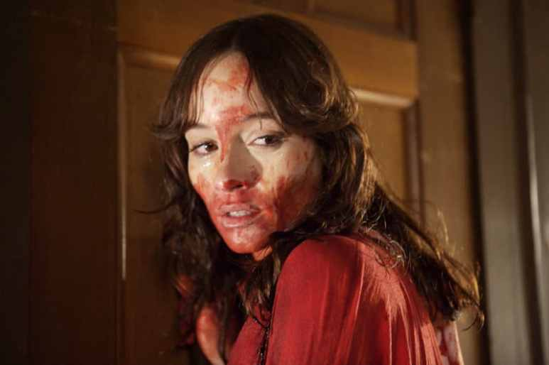 Samantha with blood on her face looking scared in The House of the Devil