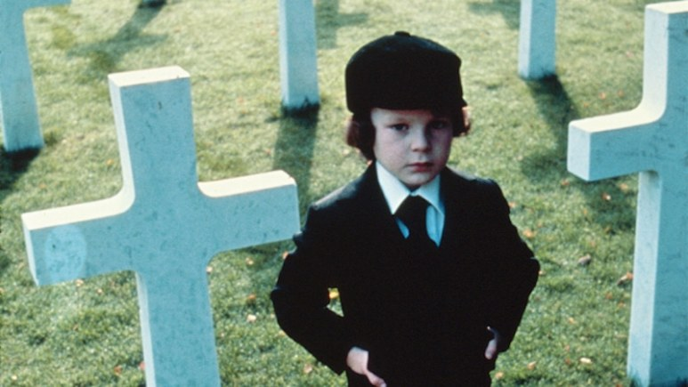Damien standing next to crosses in a cemetery in The Omen