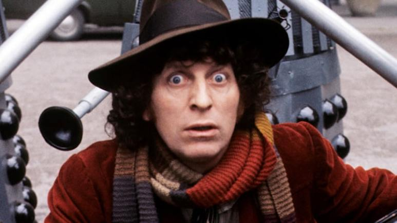 Tom Baker with a Dalek behind him as Doctor Who