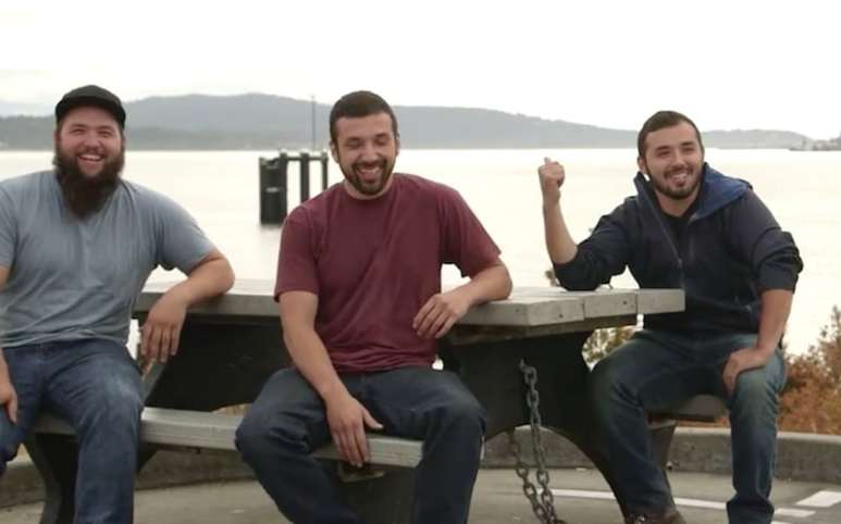 Niko, Pedro and Carlos from Carspotting laughing together while sitting on a picnic table