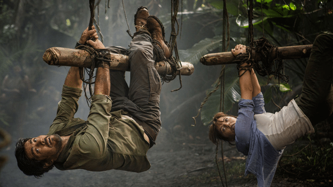 Hooten (Micheal Landes) and Lady Lindo-Parker (Ophelia Lovibond) are tied to logs by their hands and feet in the Amazon jungle and hoisted into the air