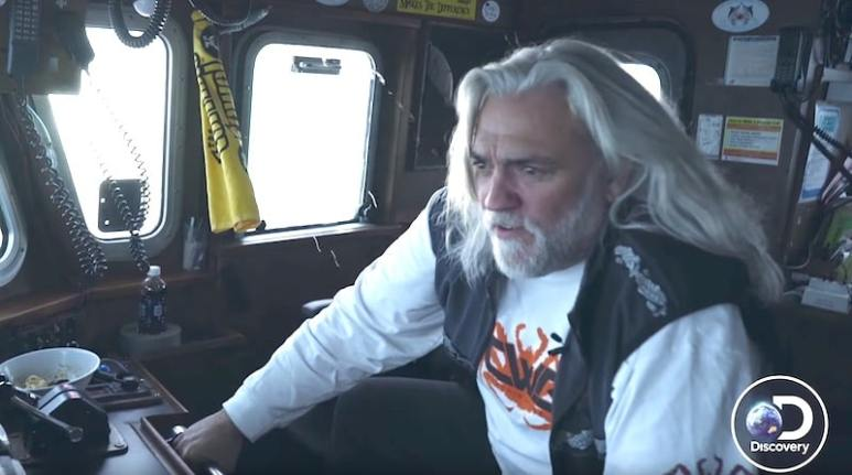 Captain 'Wild Bill' Wichrowski holding on to a metal bar in a cockpit of the Summer Bay on Deadliest Catch