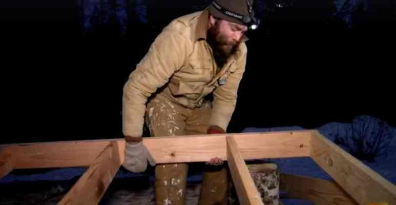 Morgan moves a wooden frame as he builds house