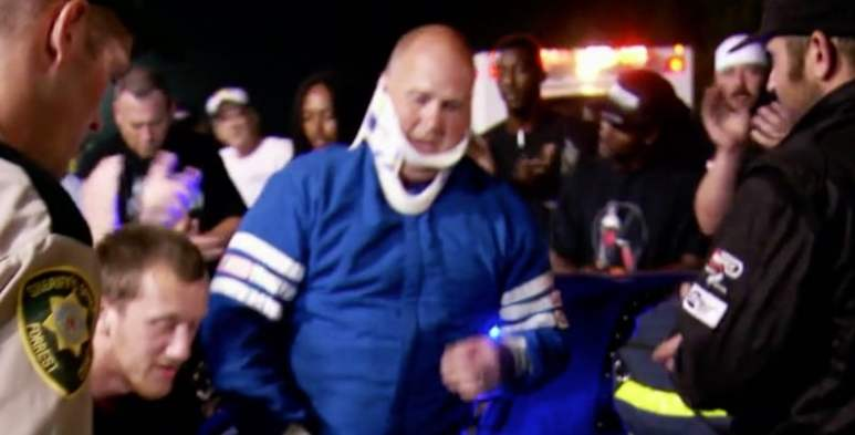 Jason Thames being helped form his car after crash with neck brace on and looking in pain