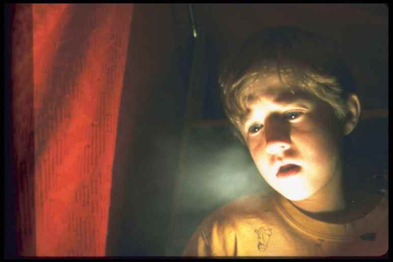 Haley Joel Osment as Cole Sear looks at a glowing light in The Sixth Sense
