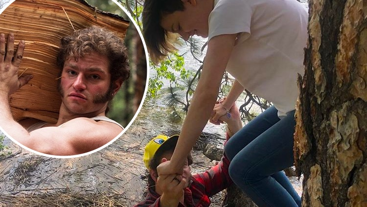 Alaskan Bush People's Gabe Brown helps his sister Rain down from a tree during a flood