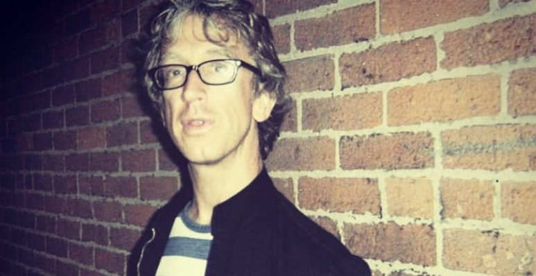 Andy Dick standing against a brick wall in a photo from Instagram