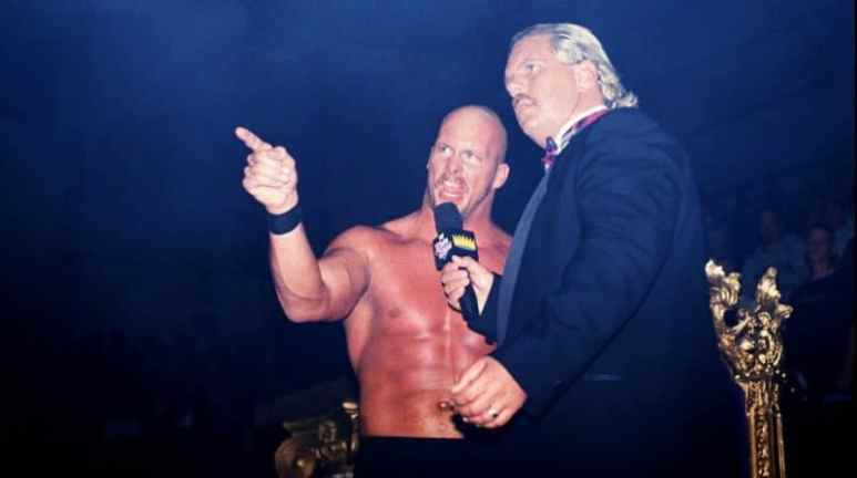 Stone Cold Steve Austin speaking into the microphone held by Michael Hayes