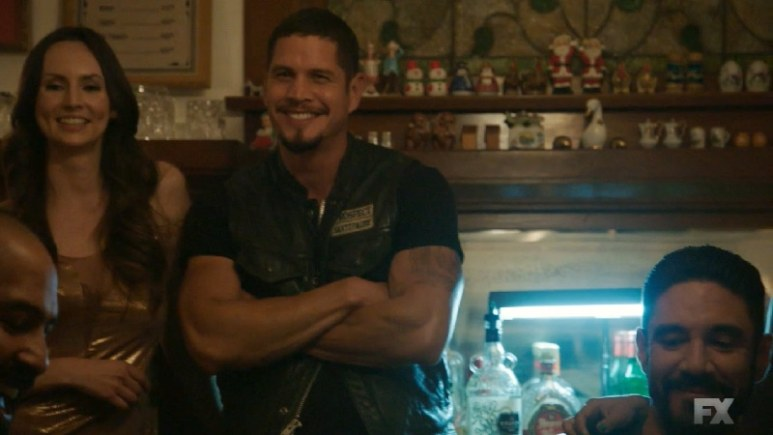 Still Image from Mayans M.C. EZ shares some laughs with the club at Victoria's brothel as gunshots are heard outside. Pic credit: FX