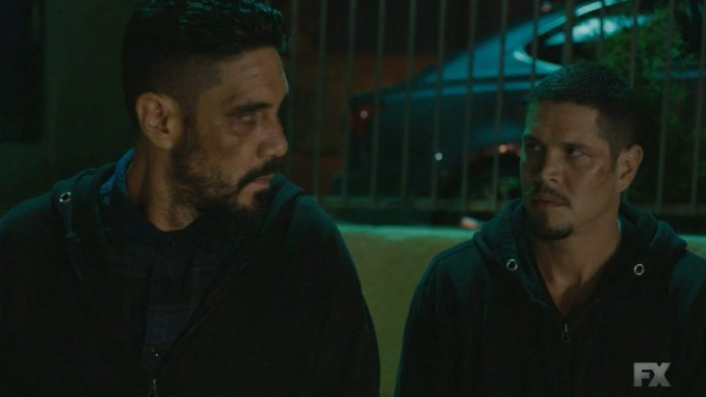 Still Image: Mayans M.C. Rata/Ch'o. While disposing of Celia's body, EZ and Angel are caught by Officer Rogan and his rookie partner who discover the body in the trunk of the car. Pic Credit: FX