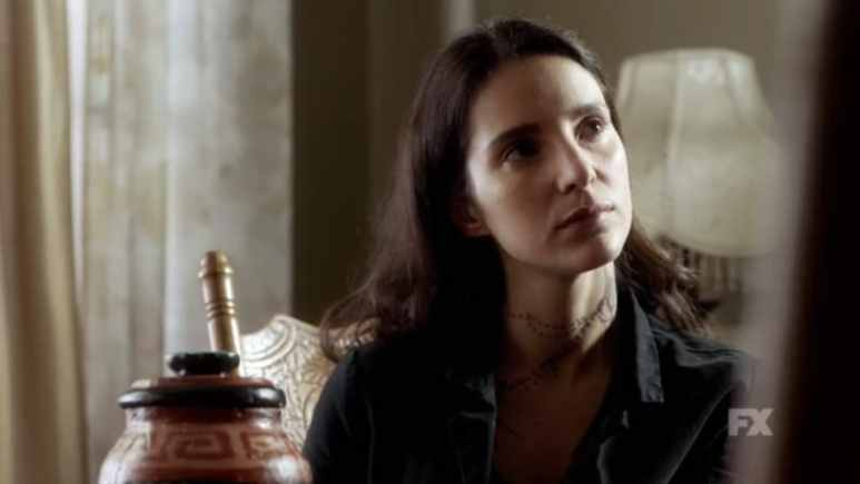 Still image from Mayans M.C. Cucaracha/K'uruch preview. Adelita moves the urn of ashes to the table as she threatens Felipe, using his real name Ignacio. Pic Credit: FX