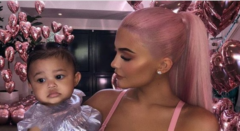 Kylie Jenner and her daughter Stormi Webster pose from inside their home in Calabasas