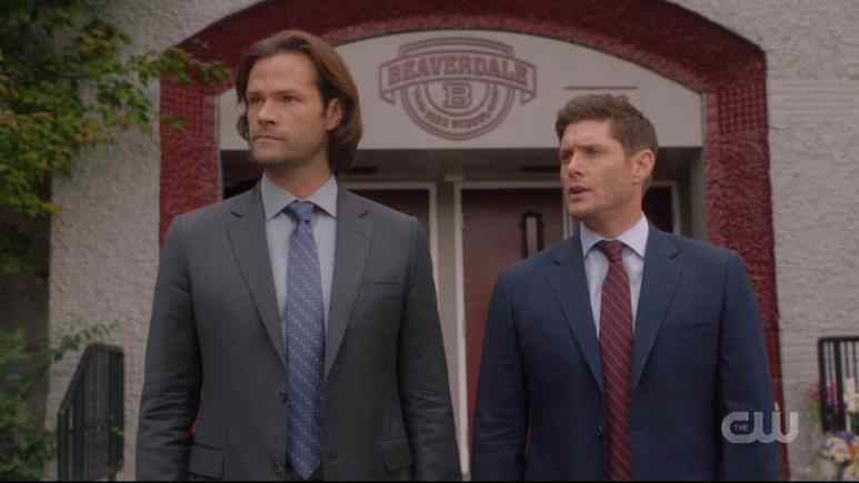 Sam and Dean standing outside Beaverdale High School in Supernatural season 15 episode 4. Pic credit: the CW