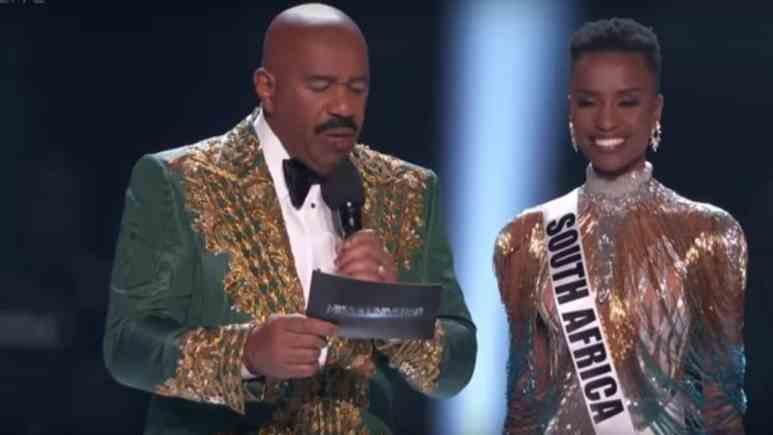 Steve Harvey on stage with Zozibini Tunzi, winner of Miss Universe 2019