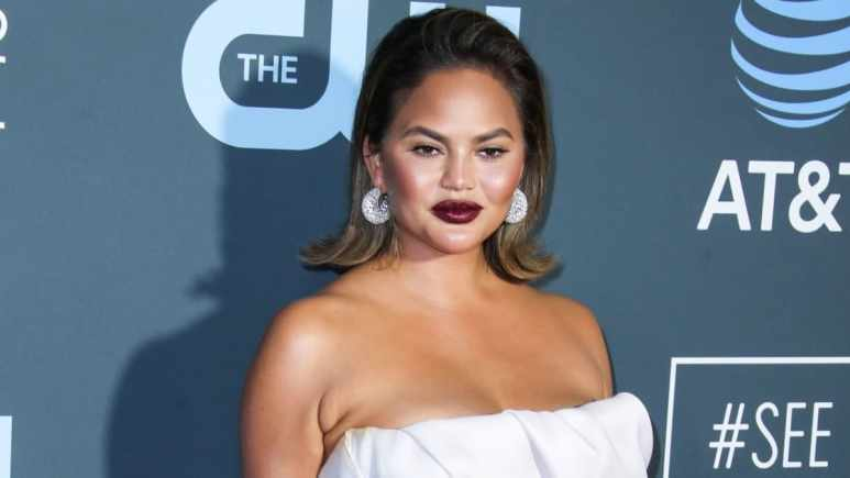 Model Chrissy Teigen wearing a Maison Yeya dress, Stuart Weitzman shoes, Jaipur Gems earrings, Yvan Tufenkjian rings and carrying a Jimmy Choo clutch arrives at the 24th Annual Critics' Choice Awards held at the Barker Hangar