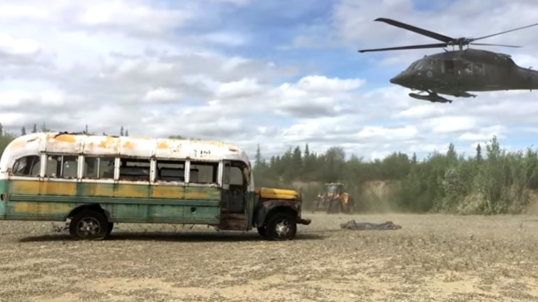 A helicopter approaches Alaska bus