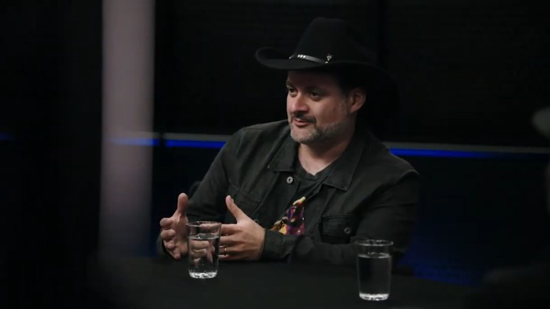 Director and writer Dave Filoni sits at a table