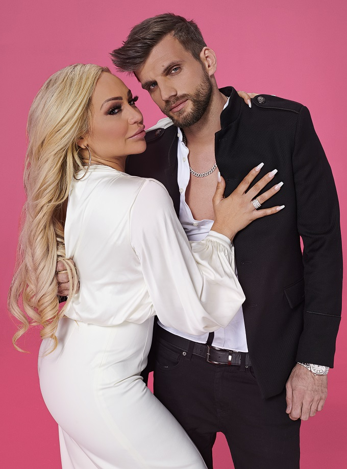 Stacey and Florian pose together against a pink background