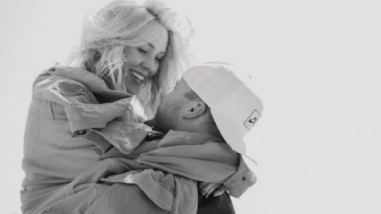 Colton Underwood holding Cassie Randolph up in his arms in a black and white photo at the beach