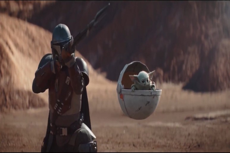 The Mandalorian stands next to The Child in his floating pod.