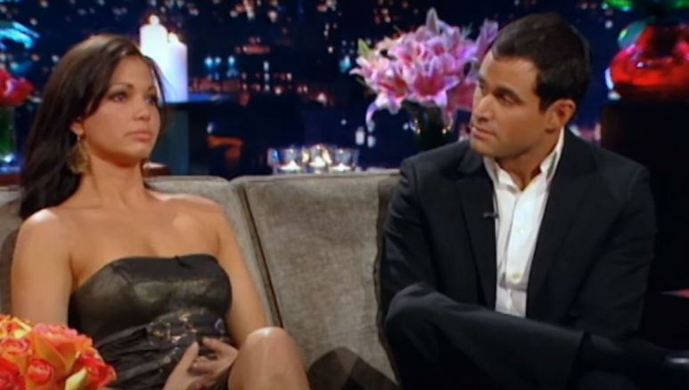 Jason Mesnick sits on the Bachelor couch with Melissa Rycroft in a black dress