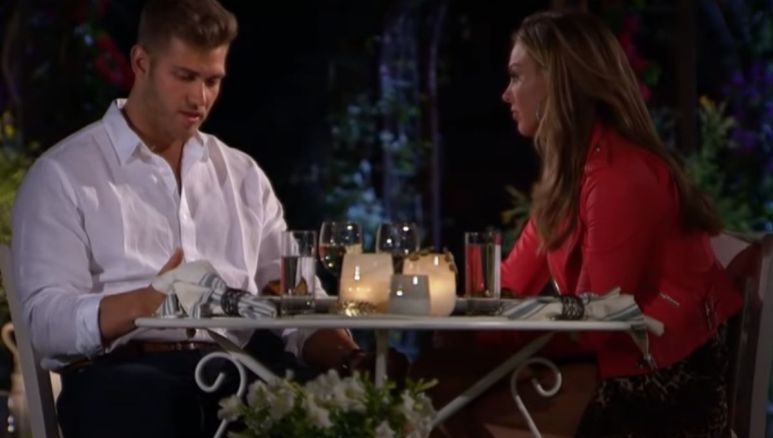 Luke Parker and Hannah Brown sit outside at night during a tense conversation