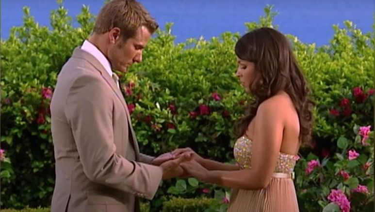 Brad Womack in a tan suit standing in front of DeAnna Pappas in a gold dress