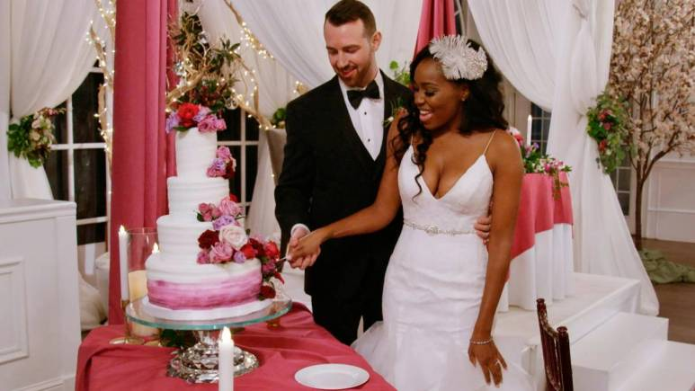 Cameron Hamilton holds Lauren Speed as she cuts their wedding cake.