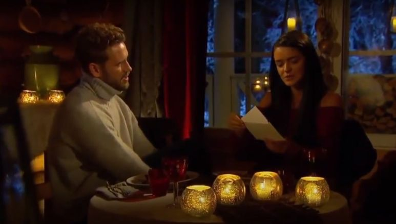 Raven Gates and Nick Viall sit at a table together surrounded by candle light