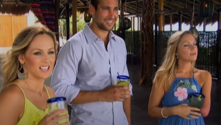 Clare Crawley stands in a yellow dress holding a drink next to two other contestants on Bachelor in Paradise