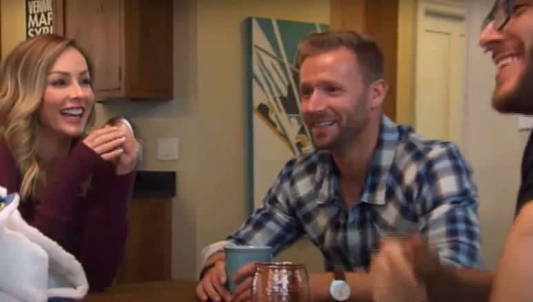 Clare Crawley sits at a table laughing and having a drink with Christian Rauch and Benoit