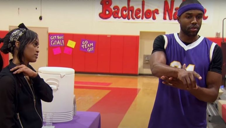Rachel Lindsay in an all black outfit stands in a gymnasium with Demario Jackson in a purple basketball jersey